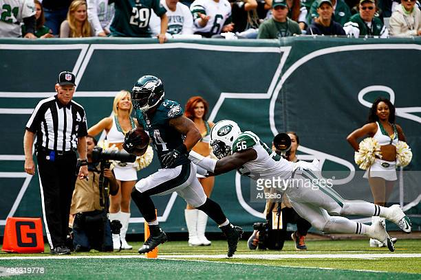 Ryan Mathews of the Philadelphia Eagles scores a touchdown in the second quarter as Demario Davis of the New York Jets defends at MetLife Stadium on...