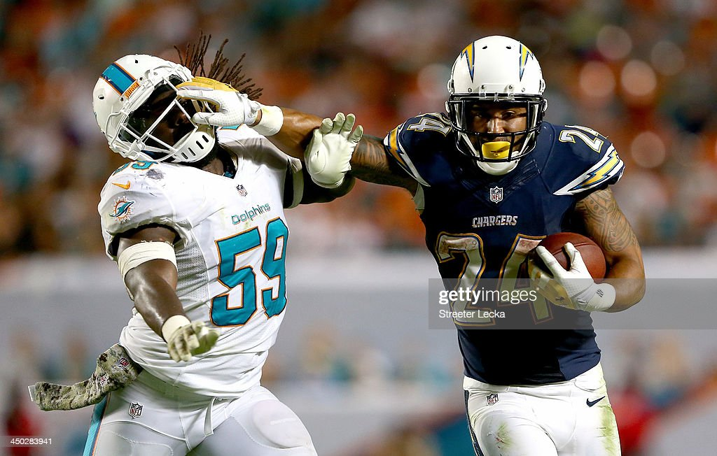 Ryan Mathews #24 of the San Diego Chargers tries to get away from Dannell Ellerbe #59 of the Miami Dolphins during their game at Sun Life Stadium on November 17, 2013 in Miami Gardens, Florida.