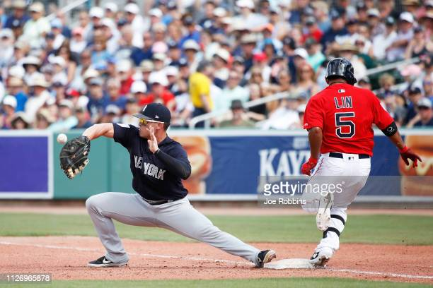 Ryan McBroom of the New York Yankees is unable to catch the ball as TzuWei Lin of the Boston Red Sox is safe at first base in the fifth inning of a...