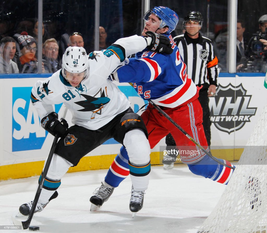 Ryan McDonagh #27 of the New York Rangers battles for the puck against Tyler Kennedy #81 of the San Jose Sharks at Madison Square Garden on March 16, 2014 in New York City.