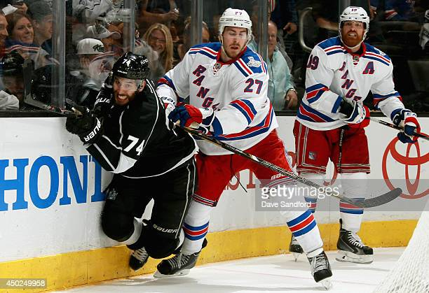 Ryan McDonagh of the New York Rangers checks Dwight King of the Los Angeles Kings during overtime of Game Two of the 2014 Stanley Cup Final at...
