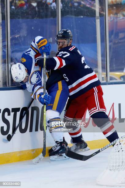 Ryan McDonagh of the New York Rangers pins Evan Rodrigues of the Buffalo Sabres along the boards during the 2018 Bridgestone NHL Winter Classic at...