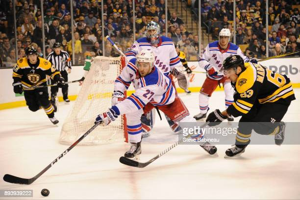 Ryan McDonagh of the New York Rangers reaches out for the puck against Brad Marchand of the Boston Bruins at the TD Garden on December 16, 2017 in...