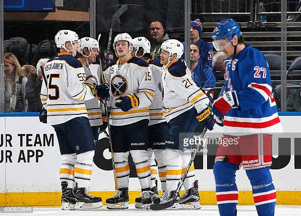 Ryan McDonagh of the New York Rangers reacts as Jack Eichel of the Buffalo Sabres is congratulated by his teammates after scoring a third period goal...
