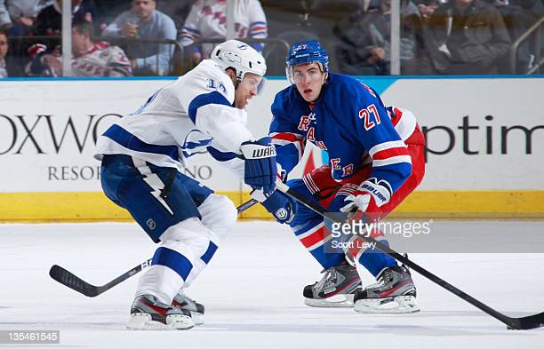 Ryan McDonagh of the New York Rangers skates against Dominic Moore of the Tampa Bay Lightning at Madison Square Garden on December 8 2011 in New York...