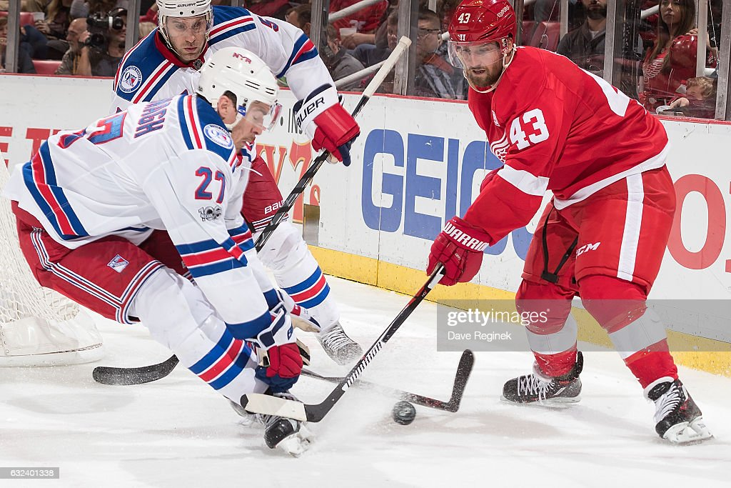 Ryan McDonagh #27 of the New York Rangers skates in after the puck with Darren Helm #43 of the Detroit Red Wings during an NHL game at Joe Louis Arena on January 22, 2017 in Detroit, Michigan.