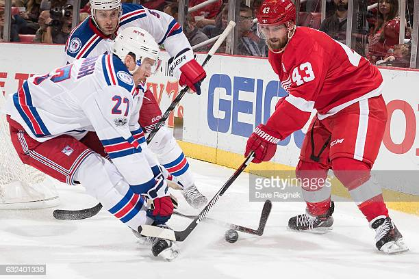 Ryan McDonagh of the New York Rangers skates in after the puck with Darren Helm of the Detroit Red Wings during an NHL game at Joe Louis Arena on...