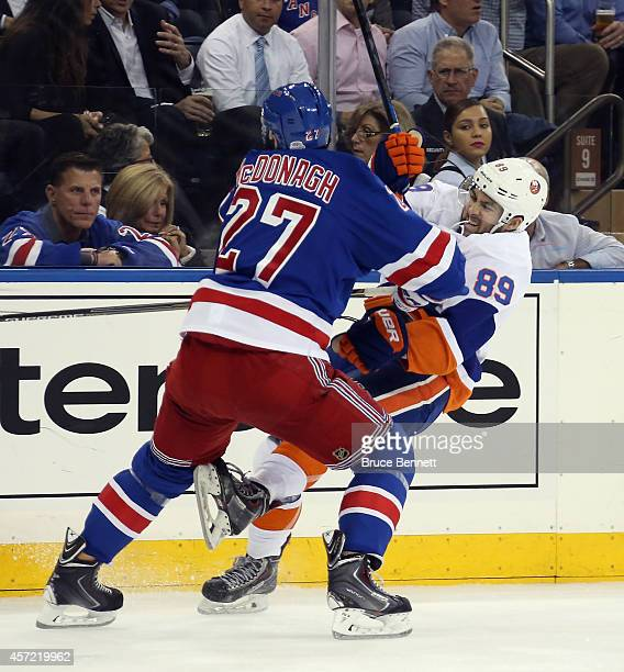 Ryan McDonagh of the New York Rangers takes an interference penalty against Cory Conacher of the New York Islanders during the first period at...