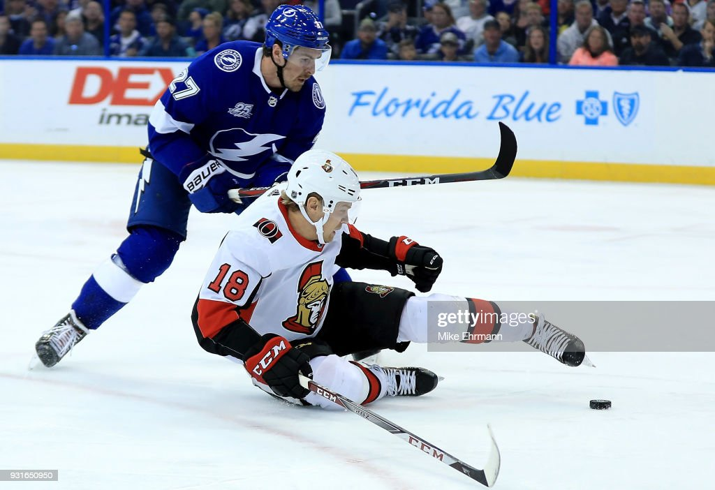 Ryan McDonagh #27 of the Tampa Bay Lightning and Ryan Dzingel #18 of the Ottawa Senators fight for the puck during a game at Amalie Arena on March 13, 2018 in Tampa, Florida.