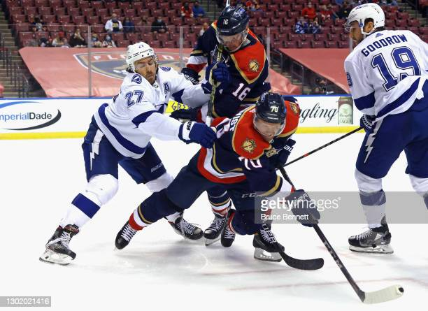 Ryan McDonagh of the Tampa Bay Lightning checks Aleksander Barkov and Patric Hornqvist of the Florida Panthers second period at the BB&T Center on...