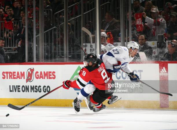 Ryan McDonagh of the Tampa Bay Lightning hits Taylor Hall of the New Jersey Devils during the third period in Game Three of the Eastern Conference...