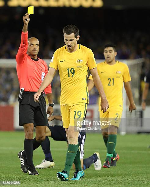 Ryan McGowan of Australia is shown the yellow card by referee Nawaf Shukralla during the 2018 FIFA World Cup Qualifier match between the Australian...