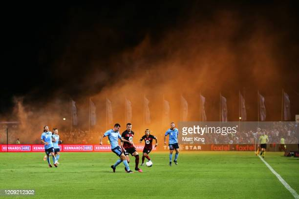 Ryan Mcgowan of Sydney FC is challenged by Mitchell Duke of the Wanderers as a flare is lit up in the crowd during the round 18 ALeague match between...