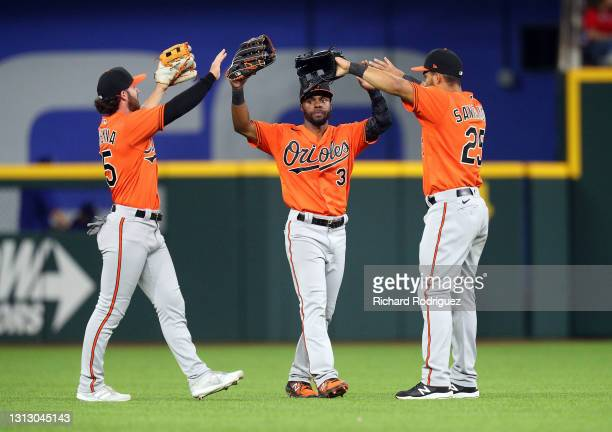 Ryan McKenna, Cedric Mullins and Anthony Santander of the Baltimore Orioles celebrate their win over the Texas Rangers after the MLB game at Globe...