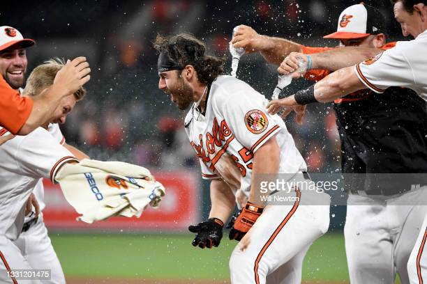Ryan McKenna of the Baltimore Orioles celebrates with teammates after being walked to drive in the winning run to defeat the Miami Marlins at Oriole...