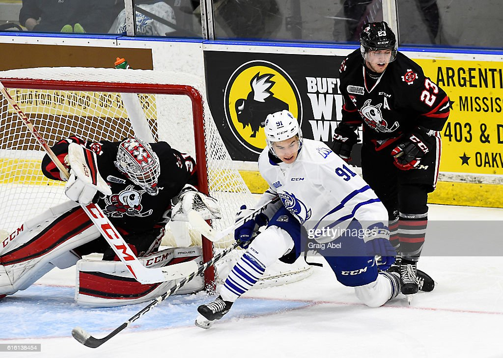 Ryan McLeod #91 of the Mississauga Steelheads is taken down by Johnny Corneil #23 of the Niagara IceDogs in front of goalie Colton Incze #31 of the IceDogs during game action on October 21, 2016 at Hershey Centre in Mississauga, Ontario, Canada.