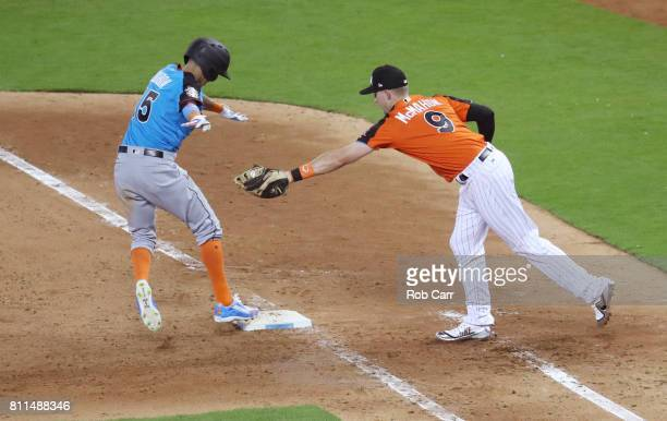 Ryan McMahon of the Colorado Rockies and the US Team tags out Mauricio Dubon of the Milwaukee Brewers and the World Team for the final out of the...