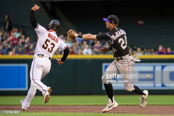 Ryan McMahon of the Colorado Rockies drops the ball while attempting to make the tag on Christian Walker of the Arizona Diamondbacks in the second...