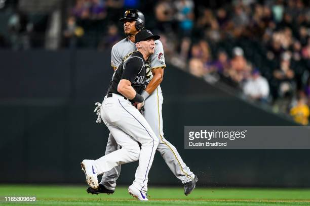 Ryan McMahon of the Colorado Rockies fields a ground ball and collides with Erik Gonzalez of the Pittsburgh Pirates on a play that was ruled a force...