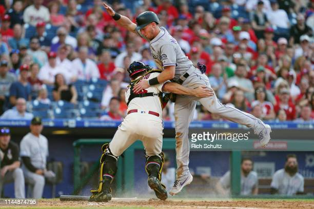 Ryan McMahon of the Colorado Rockies is out at home plate after being tagged by catcher JT Realmuto of the Philadelphia Phillies on a fielders choice...