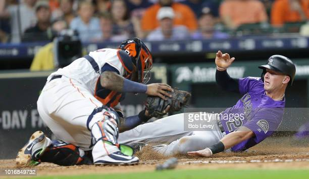 Ryan McMahon of the Colorado Rockies scores in the seventh inning as Martin Maldonado of the Houston Astros is unable to make the tag at Minute Maid...