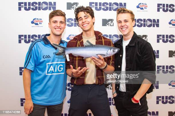 Ryan Meaney Alec McGarry and Nathan Lambert of New Rules poses backstage with Mascot James the Salmon during day 3 of Fusion Festival 2019 on...