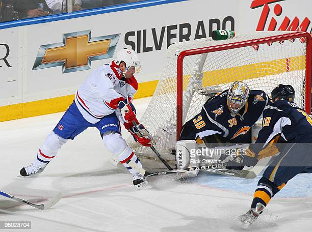 Ryan Miller and Tim Connolly of the Buffalo Sabres defend on a backhand shot by MarcAndre Bergeron of the Montreal Canadiens at HSBC Arena on March...