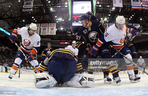Ryan Miller and Tyler Myers of the Buffalo Sabres combine to stop Matt Moulson and PA Parenteau of the New York Islanders at the Nassau Coliseum on...
