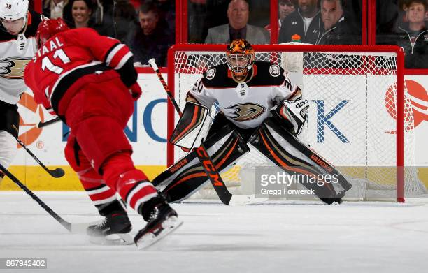 Ryan Miller of the Anaheim Ducks crouches in the crease and keeps his eye on the puck as Jordan Staal of the Carolina Hurricanes takes a shot on goal...