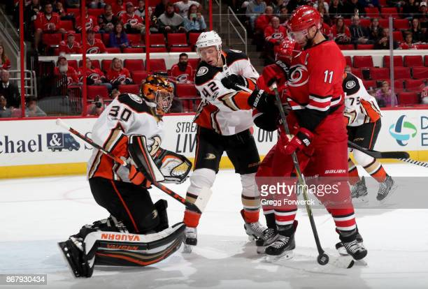 Ryan Miller of the Anaheim Ducks goes down in the crease and keeps his eye on the puck as Jordan Staal of the Carolina Hurricanes looks to score...