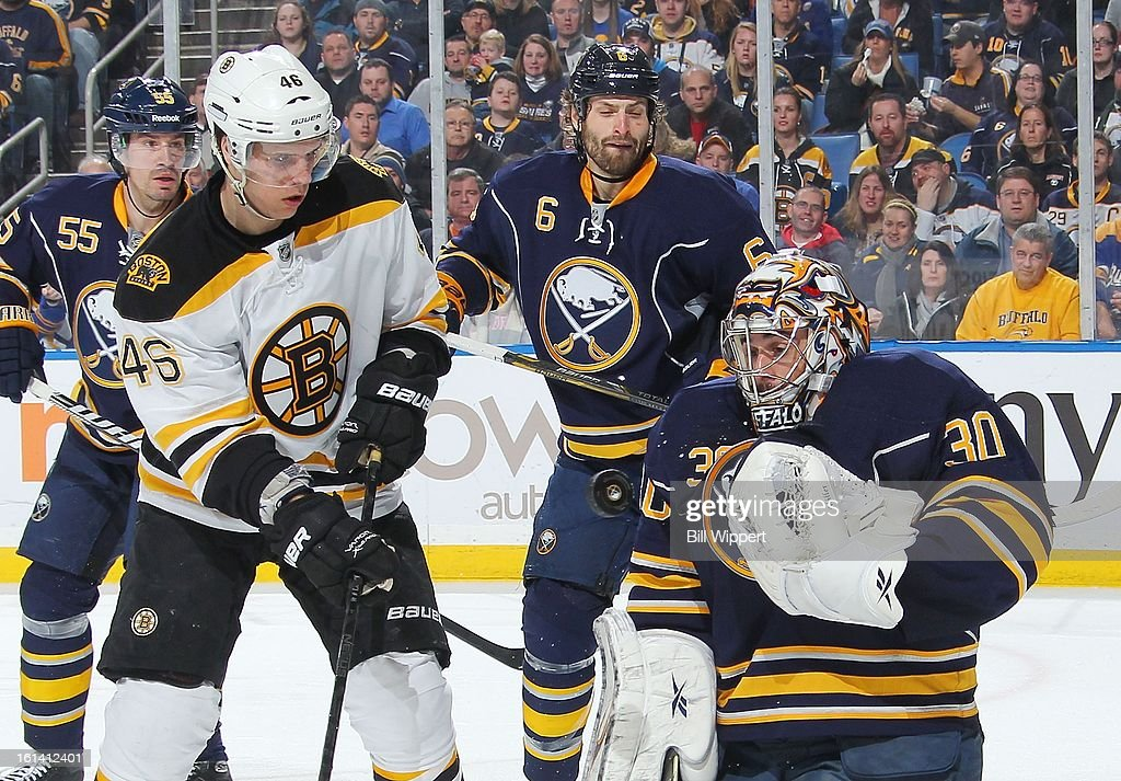 Ryan Miller #30 of the Buffalo Sabres juggles the puck alongside teammate Mike Weber #6 and David Krejci #46 of the Boston Bruins on February 10, 2013 at the First Niagara Center in Buffalo, New York.