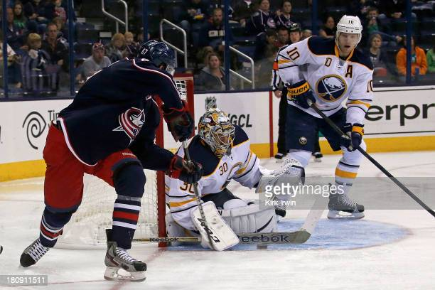 Ryan Miller of the Buffalo Sabres makes a save on a wrap around attempt by Nick Moutrey of the Columbus Blue Jackets during the second period on...