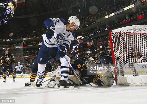 Ryan Miller of the Buffalo Sabres makes a stop on Dominic Moore of the Toronto Maple Leafs on December 12 2008 at HSBC Arena in Buffalo New York