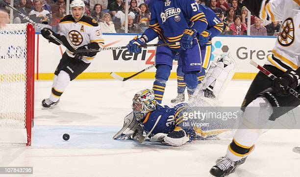 Ryan Miller of the Buffalo Sabres watches the puck bounce back out of the net after Zdeno Chara of the Boston Bruins skates by celebrating his first...