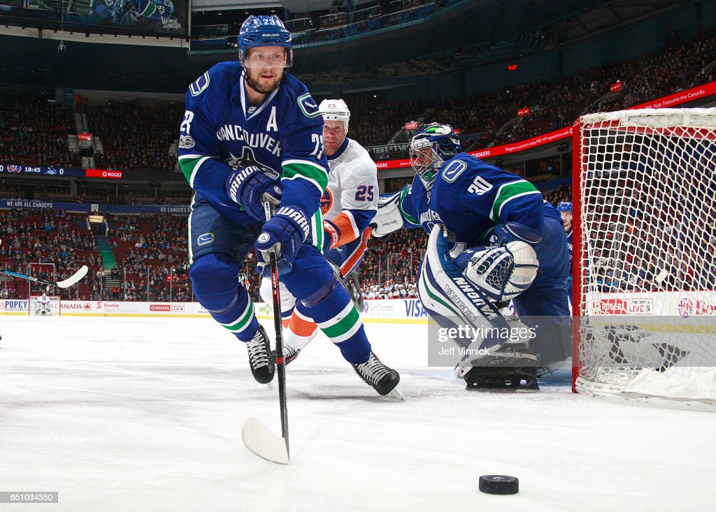 Ryan Miller #30 of the Vancouver Canucks and Jason Chimera #25 of the New York Islanders look on as Alexander Edler #23 of the Vancouver Canucks skates after a loose puck during their NHL game at Rogers Arena March 9, 2017 in Vancouver, British Columbia, Canada. New York won 4-3 in overtime.