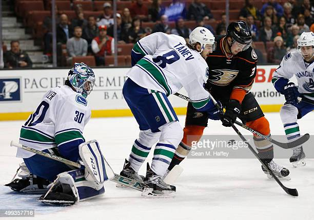 Ryan Miller of the Vancouver Canucks Chris Tanev of the Vancouver Canucks battle with Nick Ritchie of the Anaheim Ducks for a loose puck during the...