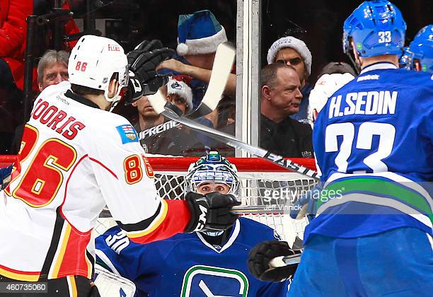 Ryan Miller of the Vancouver Canucks eyes the puck between the sticks as Josh Jooris of the Calgary Flames and Henrik Sedin of the Canucks watch...