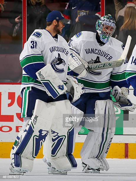 Ryan Miller of the Vancouver Canucks is congratulated by teammate Eddie Lack after Miller recorded the shut out against the Philadelphia Flyers on...