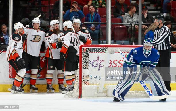 Ryan Miller of the Vancouver Canucks looks on as Patrick Eaves of the Anaheim Ducks is congratulated by teammates Sami Vatanen Antoine Vermette...