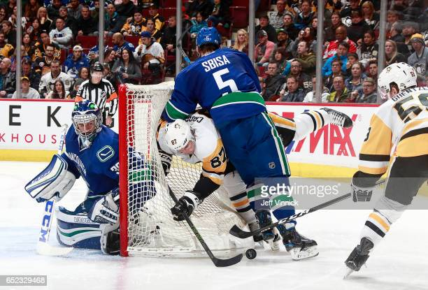 Ryan Miller of the Vancouver Canucks looks on as teammate Luca Sbisa checks Sidney Crosby of the Pittsburgh Penguins during their NHL game at Rogers...