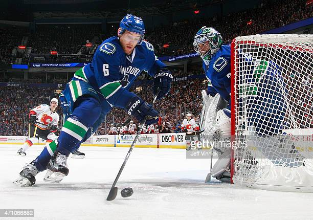 Ryan Miller of the Vancouver Canucks looks on as Yannick Weber of the Vancouver Canucks skates up ice with the puck during Game Five of the Western...