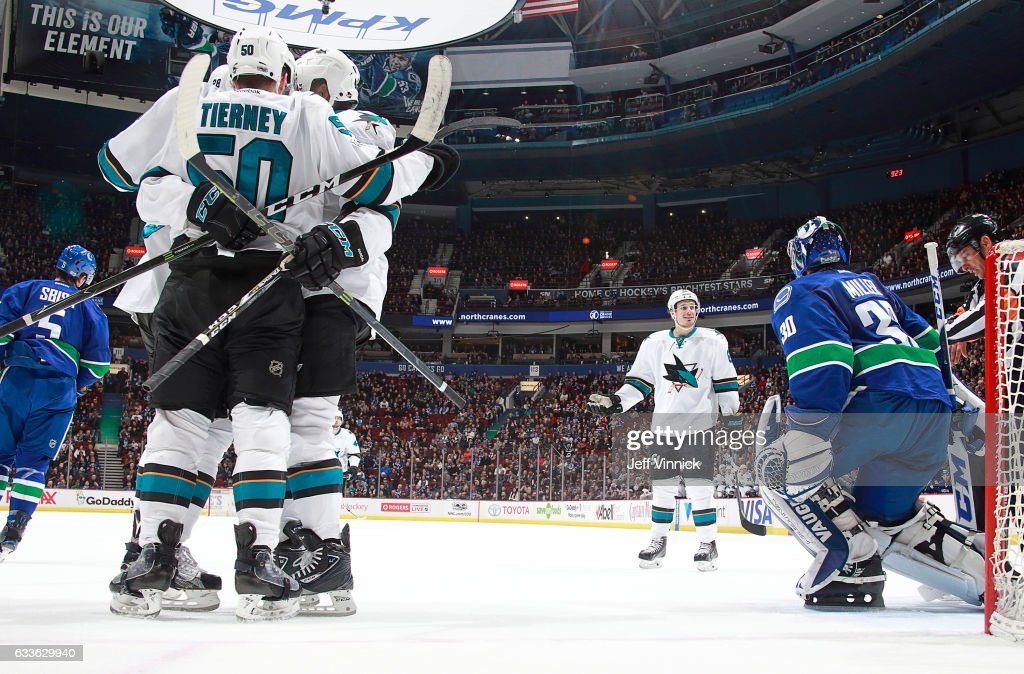Ryan Miller #30 of the Vancouver Canucks looks on dejected as Chris Tierney #50 of the San Jose Sharks is congratulated by teammates after scoring during their NHL game at Rogers Arena February 2, 2017 in Vancouver, British Columbia, Canada. San Jose won 4-1.