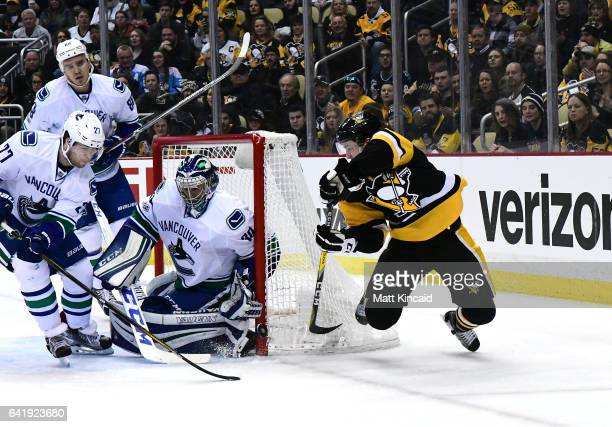 Ryan Miller of the Vancouver Canucks makes a save against Josh Archibald of the Pittsburgh Penguins at PPG PAINTS Arena on February 14 2017 in...