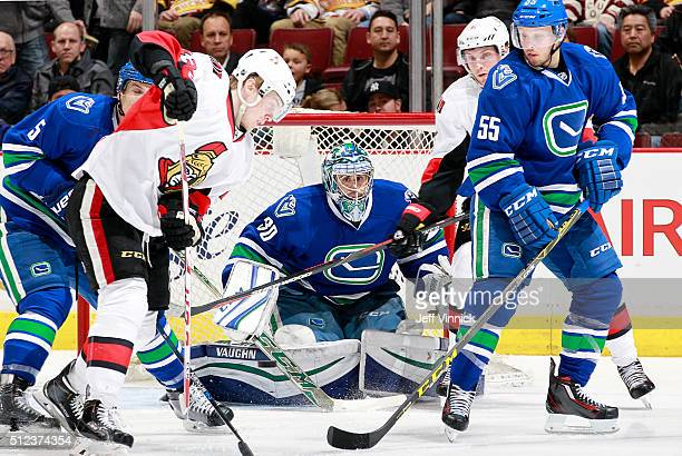 Ryan Miller of the Vancouver Canucks peers through a crowd for the puck during their NHL game against the Ottawa Senators at Rogers Arena February 25...