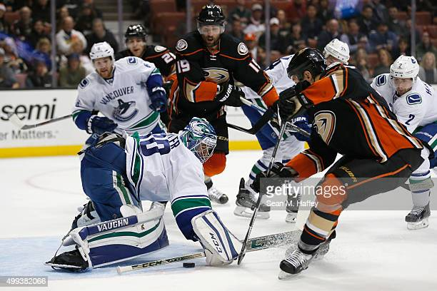 Ryan Miller of the Vancouver Canucks tends net as Chris Stewart of the Anaheim Ducks and Patrick Maroon of the Ducks stab at a loose puck during the...