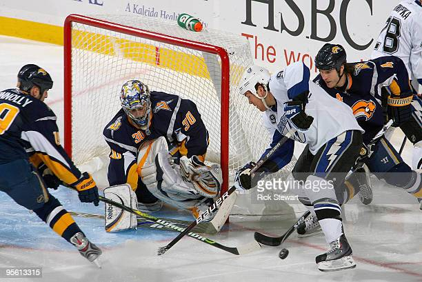 Ryan Miller Tim Connolly and Steve Montador of the Buffalo Sabres defend of a shot by Steve Downie of the Tampa Bay Lightning at HSBC Arena on...