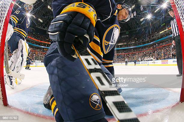 Ryan Miller watches as his teammate Henrik Tallinder of the Buffalo Sabres reaches into the back of the net for the puck after a second period goal...
