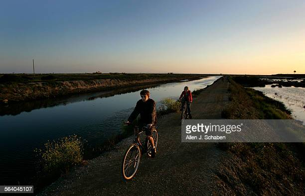 Ryan Mills left and his sister Hannah Mills of La Verne and Leah Duran of La Quinta shown in background on path ride their bikes along the...