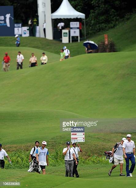 Ryan Moore and Ricky Barnes of the US walk towards the 1st green during the second round of the CIMB Asia Pacific Classic Malaysia 2010 golf...