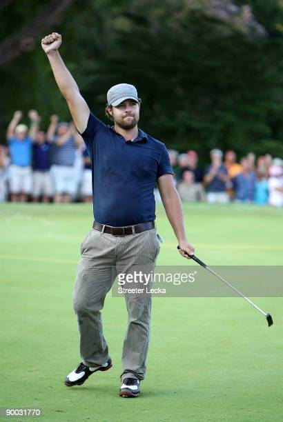 Ryan Moore celebrates after making a putt to win the Wyndham Championship in a sudden death playoff against Kevin Stadler and Jason Bohn at...